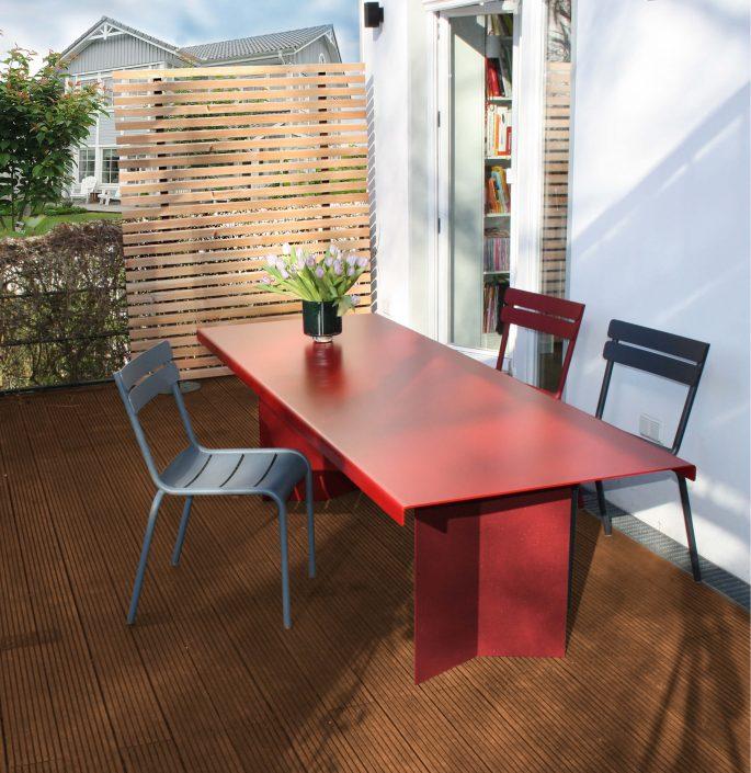 Tisch C`7 - Rotsehen. Ganz im Gegenteil erfreut man sich an diesem Tisch bester Laune (Gesellschaft). Gefertigt aus pulverbeschichtetem Aluminium kann der Tisch ganzjährig im Freien stehen und bietet Platz für gut 8 Personen. Gekantete Beine und seitlich geknickte Tischkanten geben dem Tisch eine optische Leichtigkeit und dennoch Stabilität und ist auf jeder Terrasse ein schöner Hingucker.
