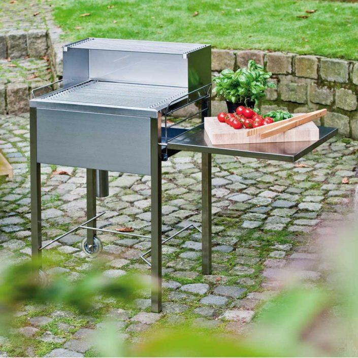Hochwertig in Deutschland gefertigter Edelstahl Holzkohlegrill mit losen Stäben und praktischen Funktionen. - Schauplatz Grill. Der handgefertigte Gartengrill aus gebürstetem, solidem Edelstahl bietet mit seinen durchdachten Details höchsten Grillkomfort. Zwei stabile Rollen sorgen für sichere Beweglichkeit im Garten oder auf der Terrasse. Durch die höhenverstellbare Glutwanne lässt sich die Hitze komfortabel regulieren. Ein praktischer Aufsatz hält fertiges Bratgut warm. Die untere Abstellfläche für Grillzubehör kann bei Bedarf seitlich befestigt werden und dient so als Beistelltisch. Der patentierte Grillrost besteht aus einzelnen Stäben, die leicht herausnehmbar sind. Nach dem Grillvergnügen können die Stäbe in dem mitgelieferten Köcher eingeweicht und gereinigt werden oder sie wandern einfach in die Geschirrspülmaschine. Die GLutwanne ist aus hitzebeständigem Stahl gefertigt, deren oberflächliche Rostbildung weder Haltbarkeit noch Grillgenuss beeinträchtigt.