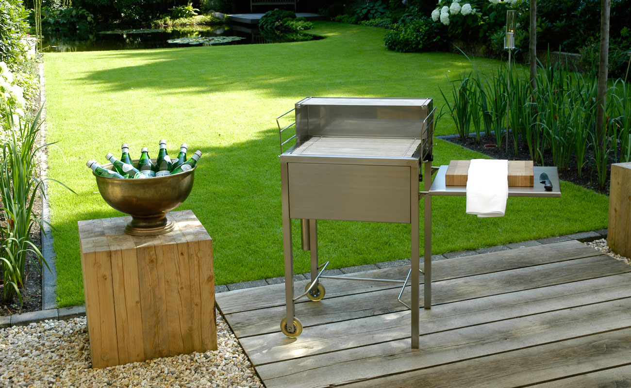 Gartengrill klein - Schauplatz Grill. Der handgefertigte Gartengrill aus gebürstetem, solidem Edelstahl bietet mit seinen durchdachten Details höchsten Grillkomfort. Zwei stabile Rollen sorgen für sichere Beweglichkeit im Garten oder auf der Terrasse. Durch die höhenverstellbare Glutwanne lässt sich die Hitze komfortabel regulieren. Ein praktischer Aufsatz hält fertiges Bratgut warm. Die untere Abstellfläche für Grillzubehör kann bei Bedarf seitlich befestigt werden und dient so als Beistelltisch. Der patentierte Grillrost besteht aus einzelnen Stäben, die leicht herausnehmbar sind. Nach dem Grillvergnügen können die Stäbe in dem mitgelieferten Köcher eingeweicht und gereinigt werden oder sie wandern einfach in die Geschirrspülmaschine. Die GLutwanne ist aus hitzebeständigem Stahl gefertigt, deren oberflächliche Rostbildung weder Haltbarkeit noch Grillgenuss beeinträchtigt.