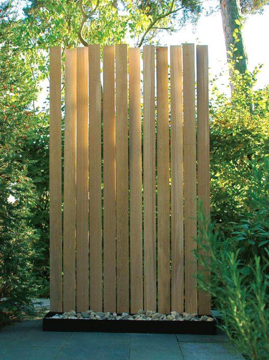 """Moderner Wind-Sichtschutz aus Eiche und verzinktem Stahl, freiaufstellbar - Unser Paravent. Inspiriert von der Natur integriert sich diese Wind-/Sichtschutz in die Umgebung. Dabei bewegen sich die einzelnen Lamellen aus Eichenholz harmonisch wie Pflanzen und erzeugen spannende Schatten und Bewegungen bei Licht, Wind und Wetter. Das Naturprodukt Holz wächst auch hier nicht nur gerade und kann noch partiell""""arbeiten"""". Der untere Sockel besteht aus zwei Stahlwannen, die nach eigenen Vorstellungen befüllt oder bepflanzt werden können."""